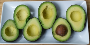 Sliced avocado halves on a white serving platter