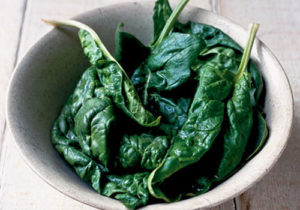 Fresh spinach leaves in a white bowl - by Doug Cook RD