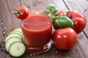 Tomato juice with tomatoes cucumber slices on a wooden table