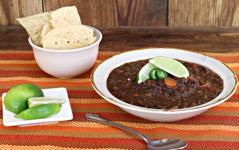 A bowl of black bean soup garnished with jalepeno and fresh lime.