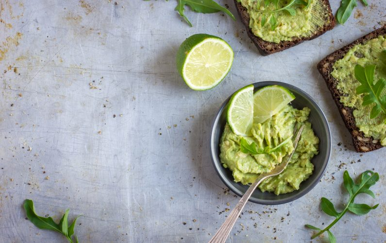 guacamole and rye toasts on rustic  background, top view, copy space