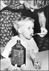Child taking cod liver oil from a spoon