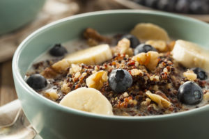 Quinoa porridge in a turquoise bowl with banana and blueberries - by Doug Cook RD