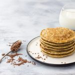 Apple zucchini flax pancakes on a plate with whole flax seeds - by Doug Cook RD