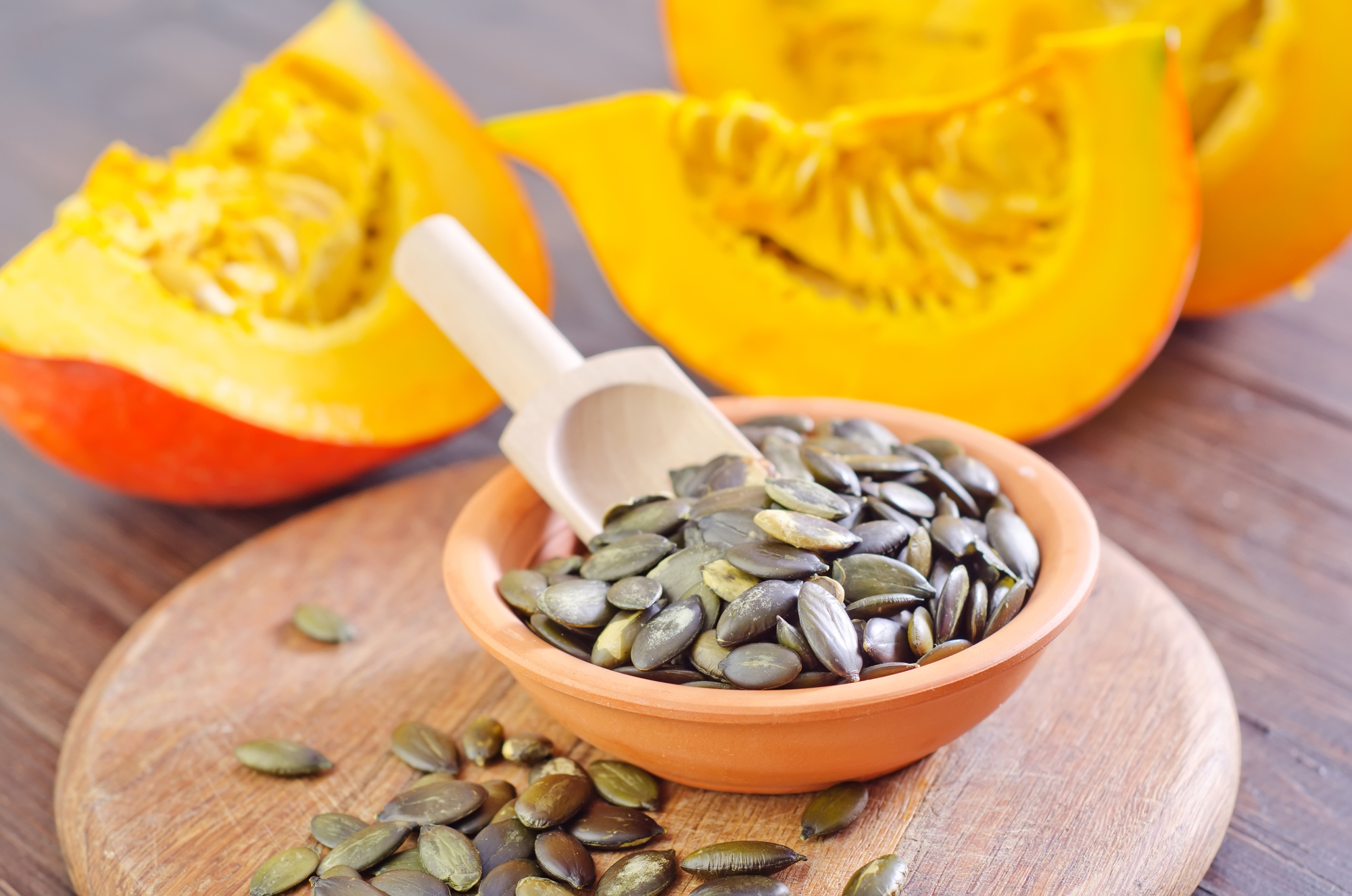Pumpkin seeds in a bowl with fresh pumpkin squash slices