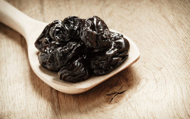 Prunes or dried plums on a wooden spoon - by Doug Cook RD