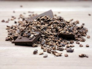 Raw cacao nibs and chocolate squares on a table top - by Doug Cook RD