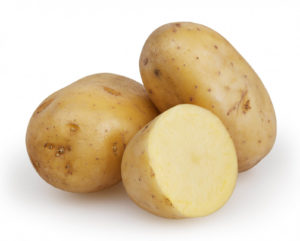 Fresh uncooked potatoes with one of them cut in half
