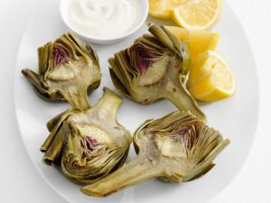 Cooked prebiotic rich artichoke on a plate with lemon