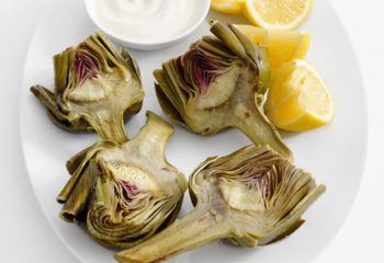 Cooked prebiotic artichoke on a plate with lemon