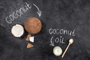 Coconut nut and coconut oil on a chalk board background