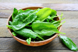 Fresh spinach in a wooden bowl - by Doug Cook RD