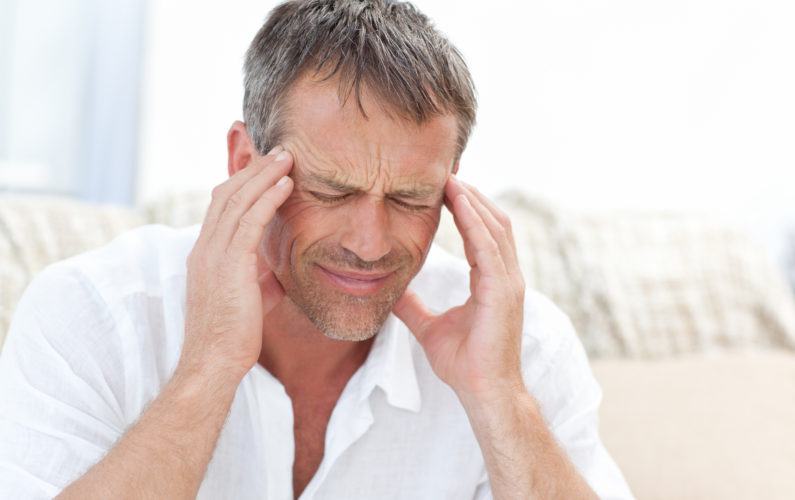 Man having a headache at home