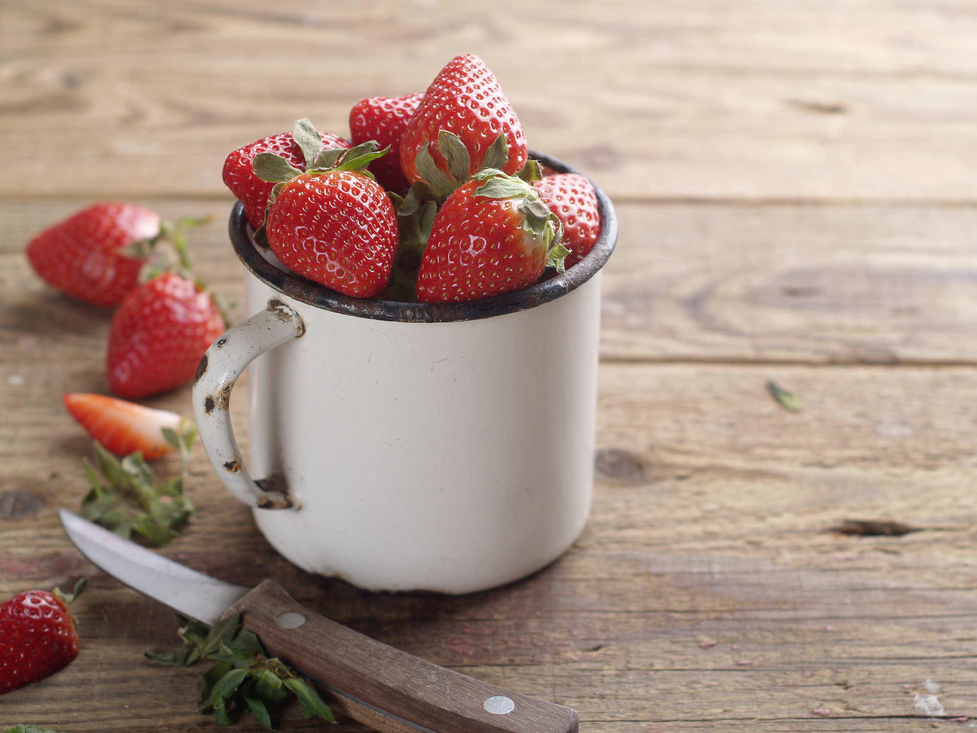 Fresh strawberries in a tin mug on a wooden table top