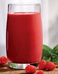 raspberry beet smoothie in a tall glass with mint leaves