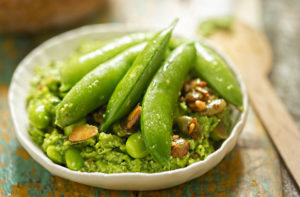 Avocado and edamame dip in a bowl with fresh snap peas