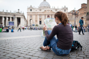 A woman sitting in a square reading a map