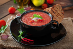 Gazpacho soup in a black serving bowl