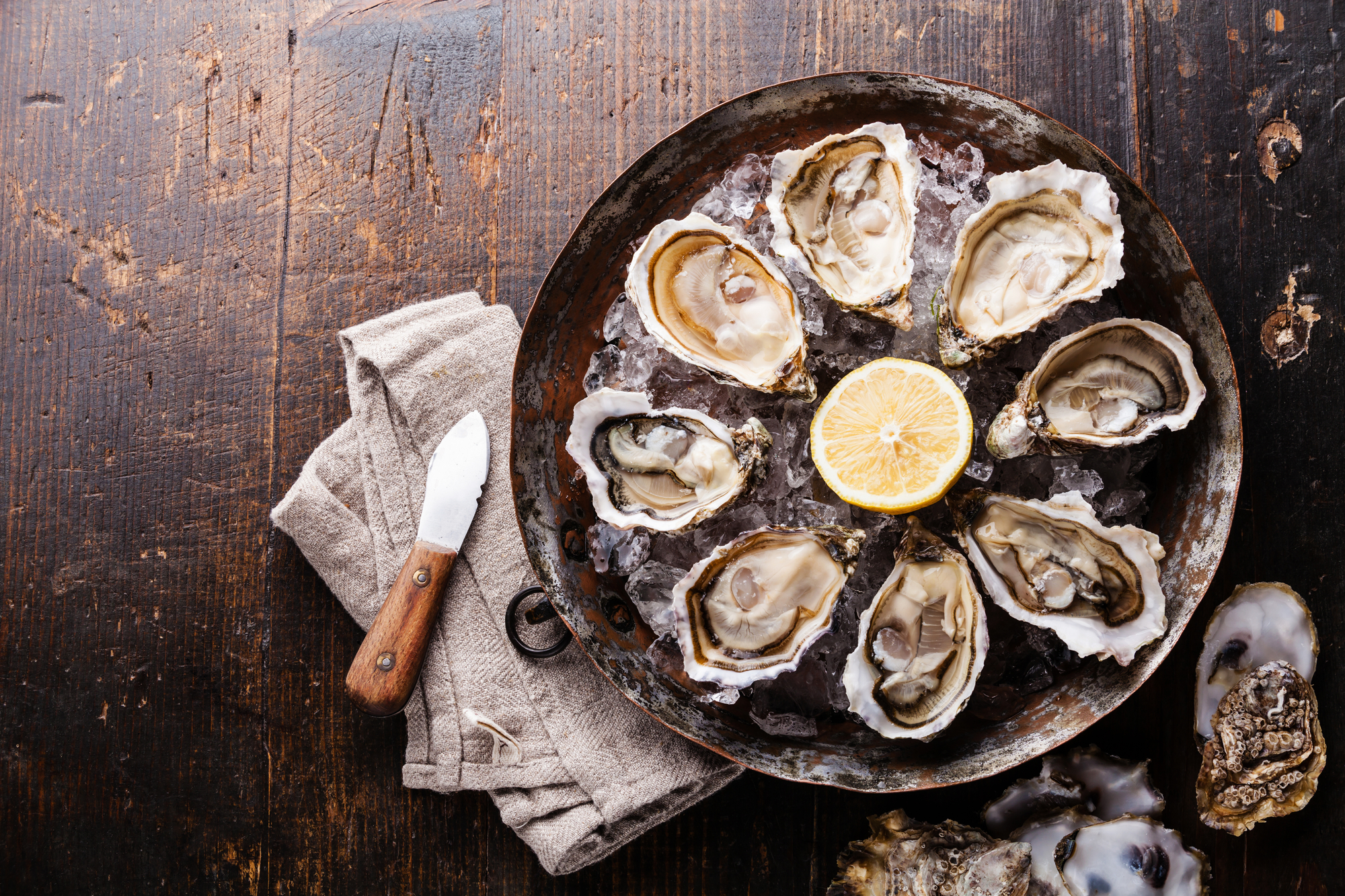 Fresh oysters on ice with lemon on a wooden table top