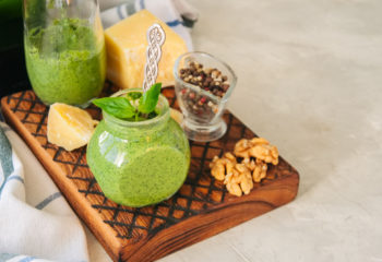 Basil walnut pesto in a jar with raw ingredients on a wooden boa