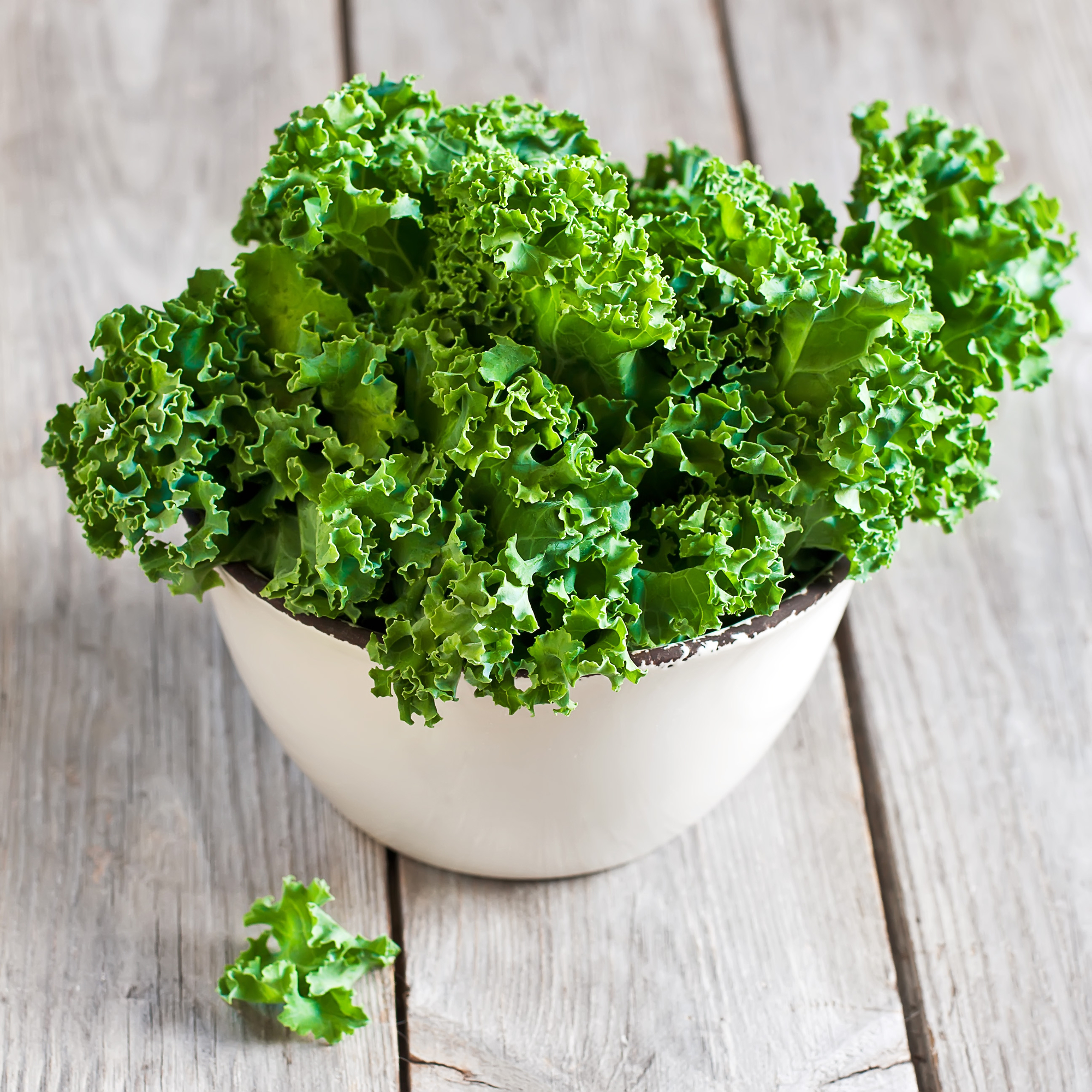 A white bowl full of fresh kale leaves on a table