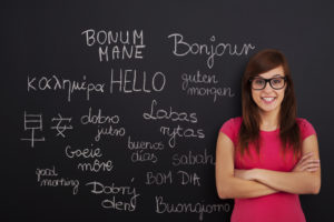 A woman standing at chalk board with the word hello in different languages