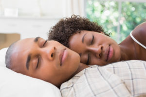 Couple sleeping soundly in bed