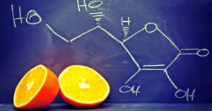 Vitamin C molecule on a chalk board with a sliced orange - found in liposomal vitamin C