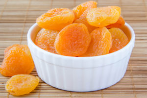 A ramekin dish filled with dried apricots on a wicker place mat