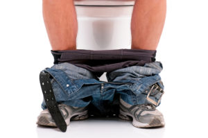 Man is sitting on the toilet bowl, on white background