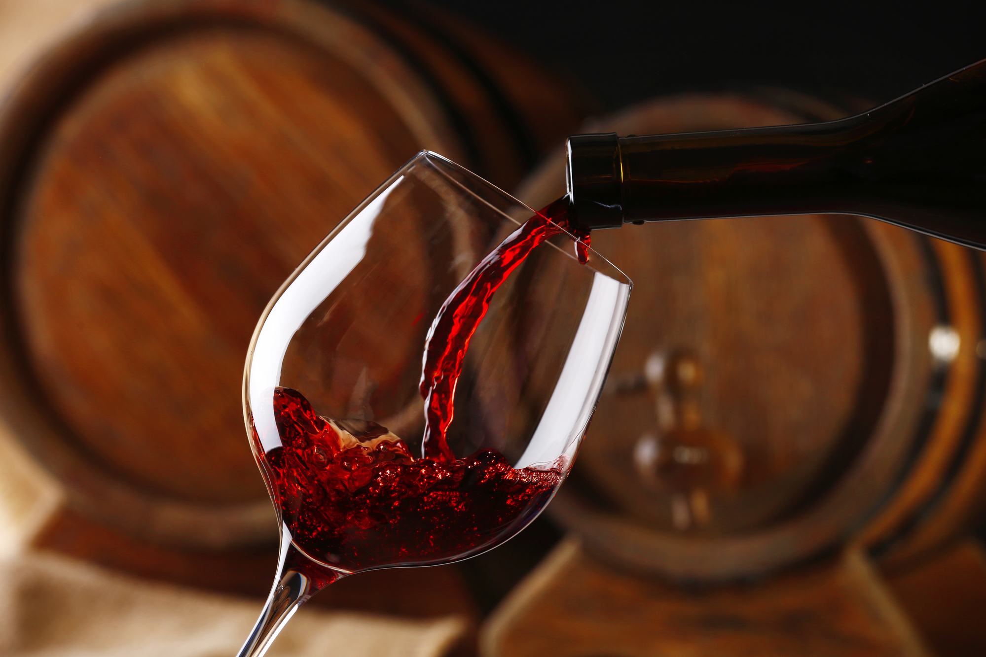 Pouring red wine from bottle into glass with wooden wine casks on background - by Doug Cook RD