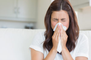 Woman sneezing in a tissue in the living room - by Doug Cook RD