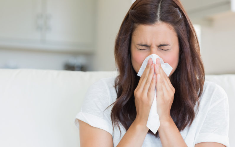 Woman sneezing in a tissue in the living room