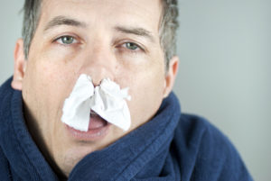 Man with a cold and runny nose with tissue