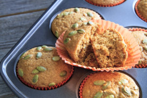 Homemade pumpkin muffins with single muffin sliced open sitting in muffin pan on rustic wooden table