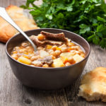 Moroccan harira soup with chickpeas and lamb, flat bread, parsley on a wooden background