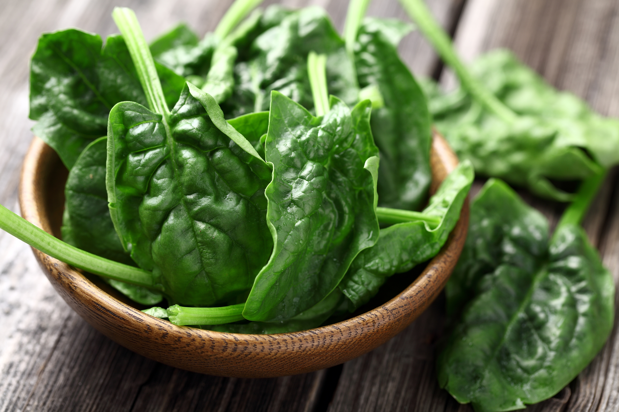Spinach leaves in a wooden bowl on a table