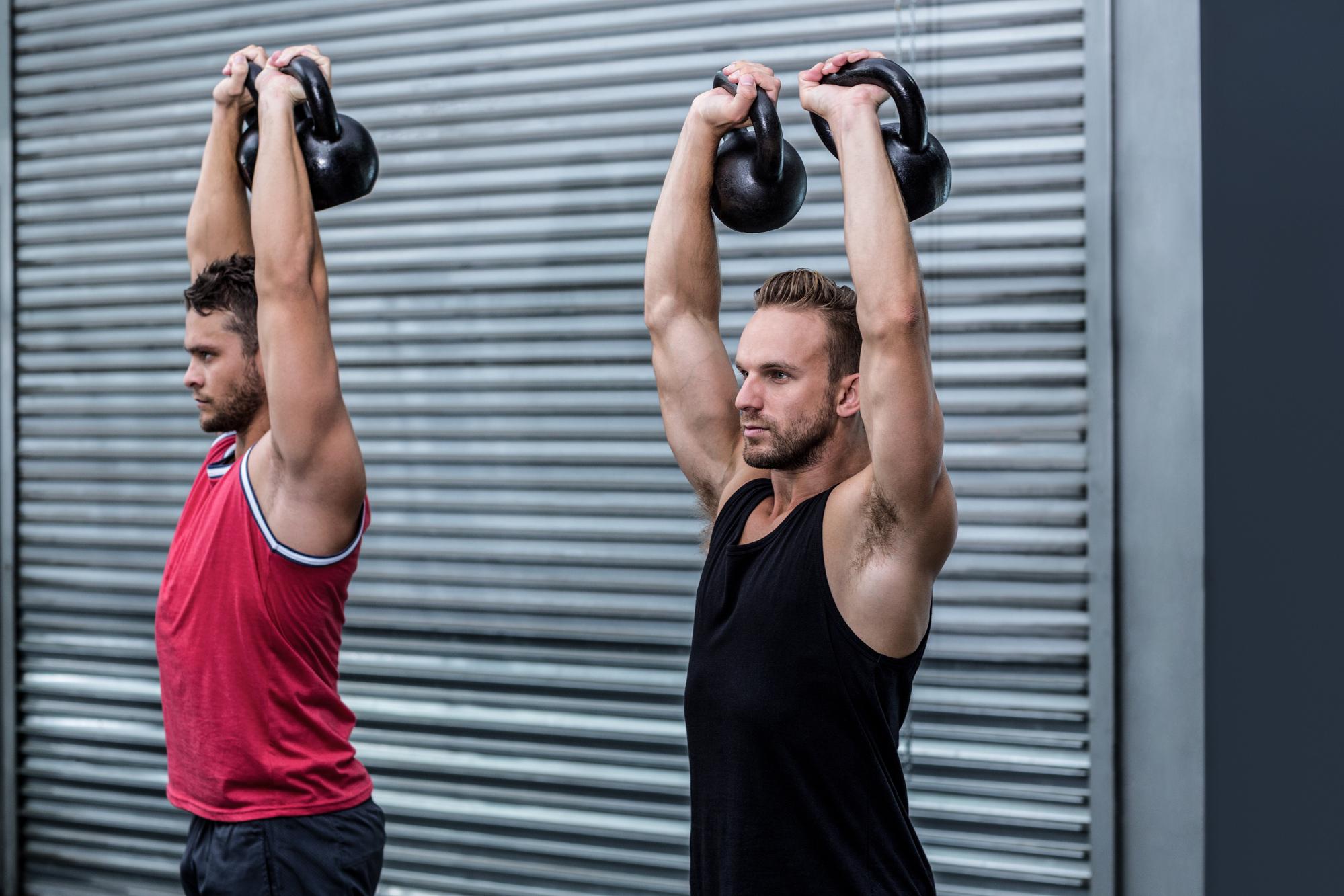 Two muscular men lifting a kettle bell