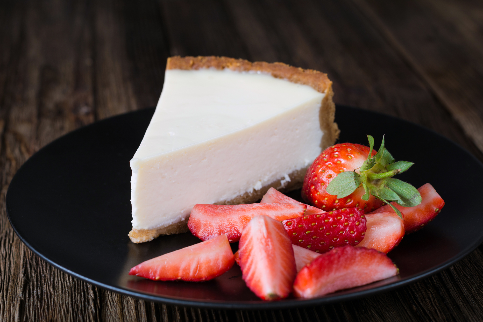 Plain cheesecake on a black plate with strawberries