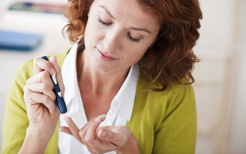 Woman with diabetes testing her blood sugar