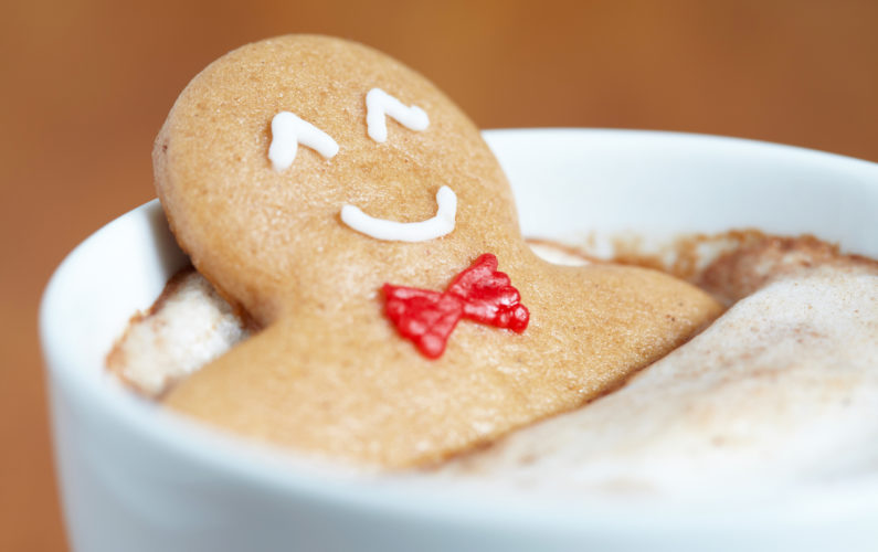 Gingerbread cookie men in a hot cup of cappuccino