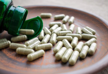 Green tea extract supplements and bottle on a clay brown plate