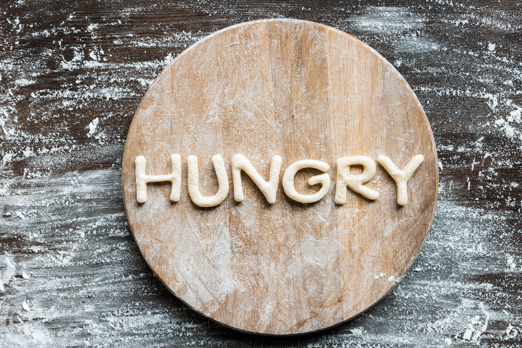 The word hungry spelled with dough on a cutting board
