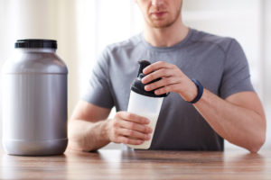 Protein shake bottle and jar of creatine powder