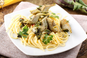 Spaghetti with artichokes and parsley on complex background