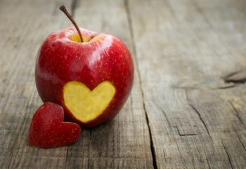 A red apple with engraved heart on a wooden table - by Doug Cook RDn