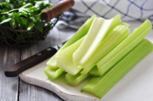 Fresh green celery stems on wooden cutting board - by Doug Cook RD
