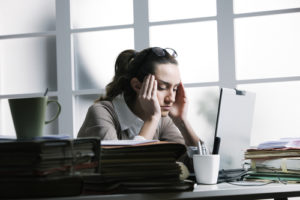 Stressed woman at desk 300x200 - Why Stress Causes Weight Gain