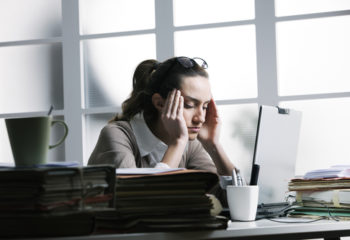 Stressed woman at her desk with a headache - by Doug Cook RD