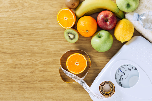 Weight scale with healthy food and measuring tape - by Doug Cook RD